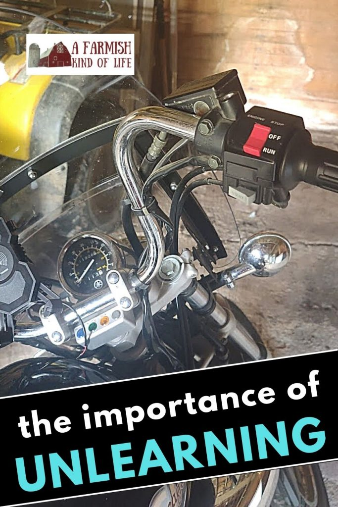 """Handlebars of a motorcycle with the words """"the importance of unlearning"""" written across it"""